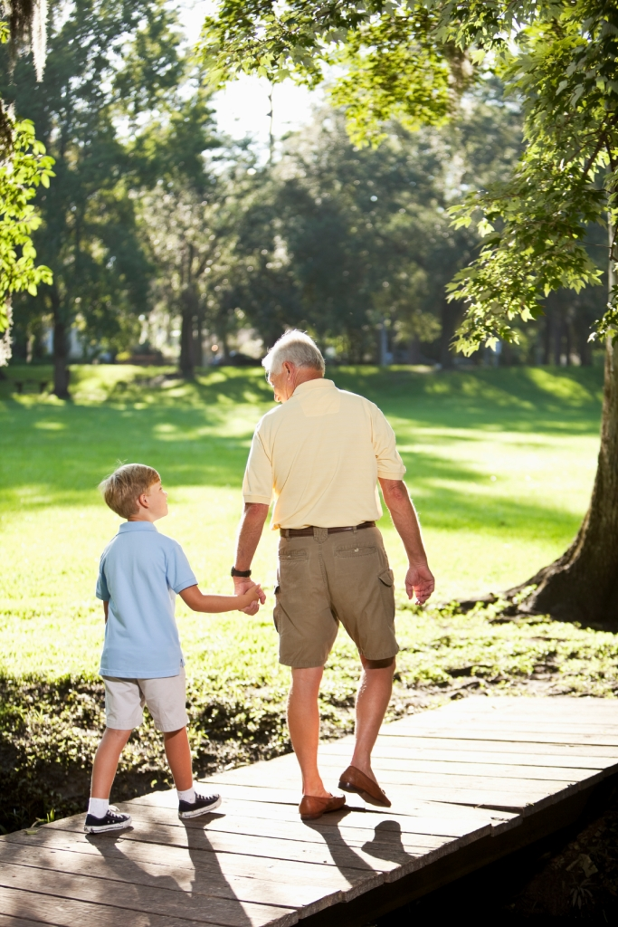 Senior man (60s) and grandson (9 years) holding hands, walking in the park.